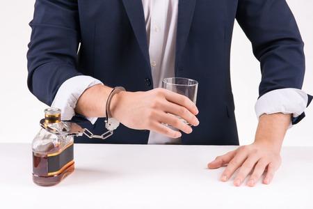 symbolic: Harmful addiction. Symbolic photo of businessperson chained to alcohol. Stock Photo