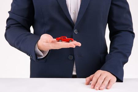 upholding: Little souvenir. Person upholding little antique car model in his hand.