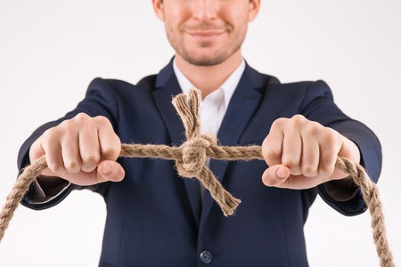 upholding: Man with rope. Person upholding thick rough knotted rope.
