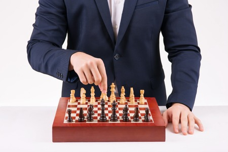 putting up: Game of chess. Person is busy putting up white figures on chess board.