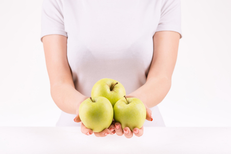 upholding: Organic apples. Woman upholding three big appetizing green apples.