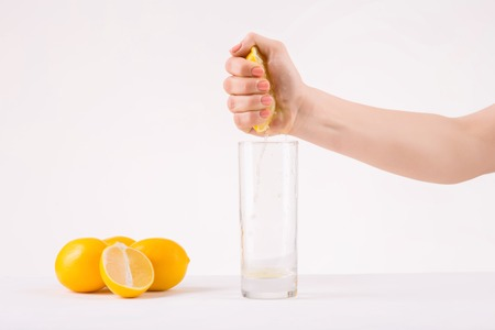 upholding: Fresh-made juice. Female hands squeezing piece of orange juice above glass to get the freshest juice.