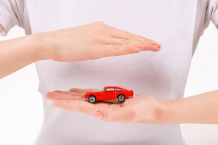 upholding: Little souvenir. Person upholding little antique car model in her hand.