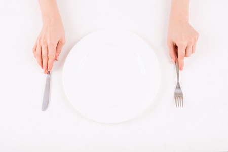 womankind: Table appointments. Female hands putting silverware onto dining table on both sides of the plate