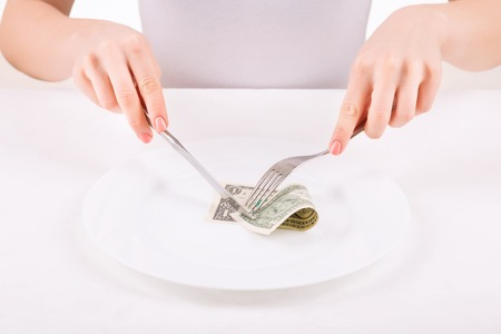 Irrational act. Woman using tableware to try and cut one dollar bill.