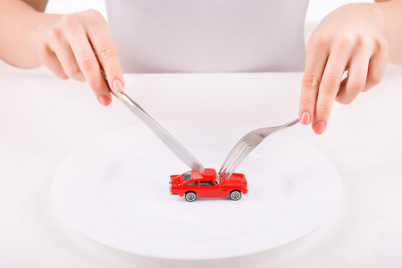womankind: Irrational combination. Woman using tableware to try and cut little car model.