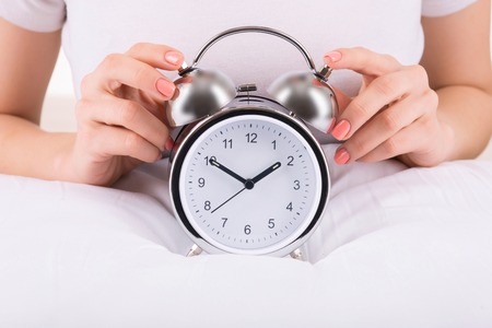 womankind: Alarm clock. Female hands touching the alarm clock