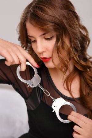 young  cuffs: Appealing young woman is sitting on bed and posing with handcuffs.