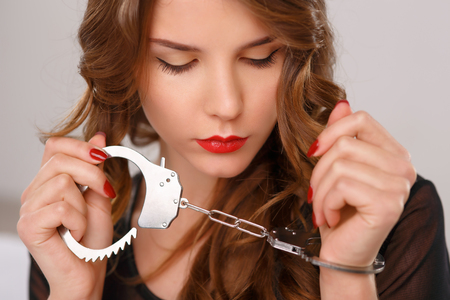 Attractive young woman is sitting on bed with one arm locked in handcuffs. Stock Photo