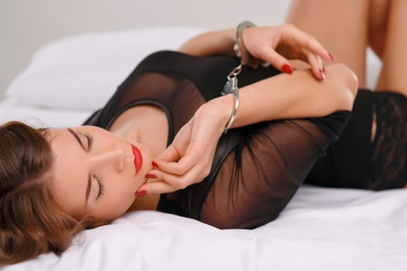 cuffs: Appealing young woman is lying on bed with her arms locked in cuffs. Stock Photo