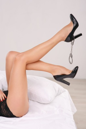 cuffs: Shot of beautiful slender woman legs wearing shoes and cuffs hanging from one high heel. Stock Photo