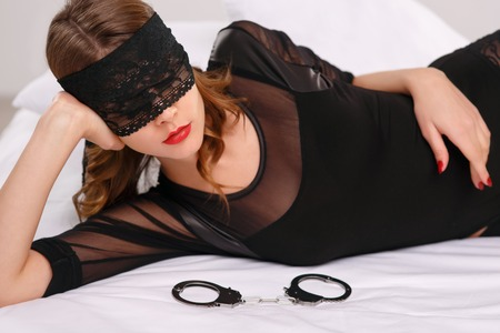 young  cuffs: Appealing young woman is resting on the side and wearing eye shade while handcuffs lying beside her.