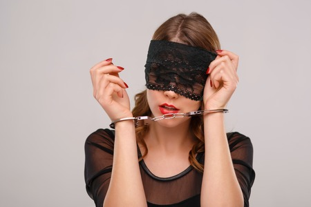 young  cuffs: Young appealing woman in eye shade is locked with handcuffs.