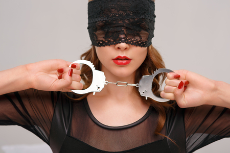 woman close up: Attractive young woman in eye shade is holding handcuffs.
