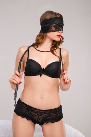 Young appealing woman is holding leather whip over her shoulders