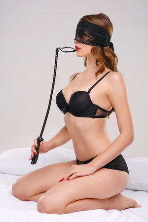 sexual foreplay: Young alluring woman is posing with leather whip seductively. Stock Photo
