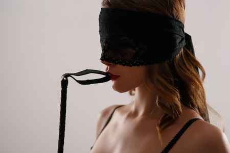 eyeshades: Young alluring woman is posing with leather whip seductively. Stock Photo