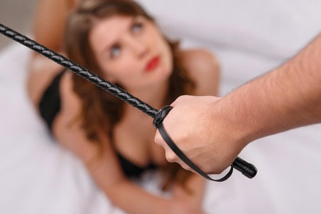 sexual foreplay: Close up of man hand holding thin leather whip while woman is lying on bed waiting.