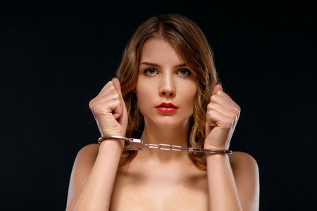 Attractive young woman is standing and upholding her locked arms Stock Photo