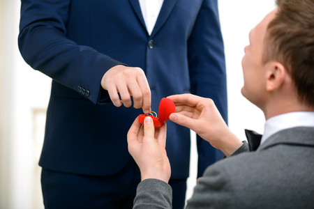 Close up of pleasant happy guy standing on the knee while making proposal hid male partner Stock Photo