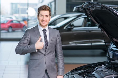 vivacious: Cheerful vivacious sale assistant standing near car and working in auto show while thumbing up