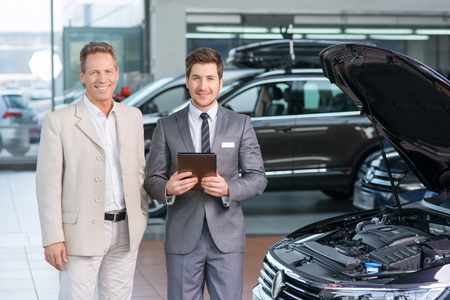 upbeat: Content upbeat sale assistant standing near car and smiling while showing it to customer.