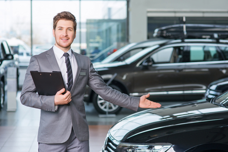 vivacious: Vivacious positive professional sale assistant holding folder and showing car while being involved in work