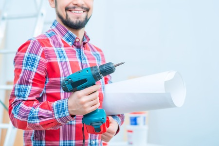 feeling up: Close up of drill in hands of pleasant smiling man holding it and feeling content while doing renovation