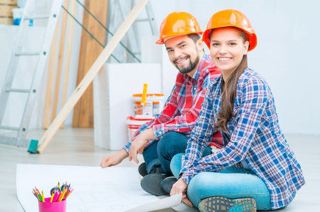 Young pleasant vivacious couple sitting on the floor and feeling happy while discussing project of their house
