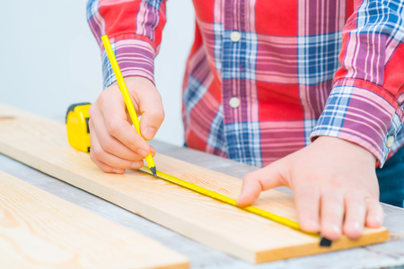 spirit level: Close up of pencil in hands of professional man holding it and using spirit level while preparing for renovation
