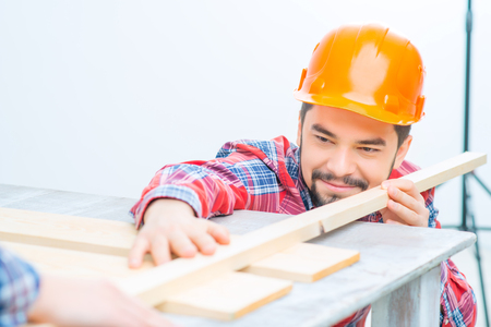 wood stick: Close up of pleasant handsome man holding wood stick while making renovation with his girlfriend Stock Photo