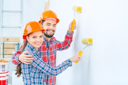 vivacious: Pleasant vivacious smiling couple standing near wall and painting it while embracing