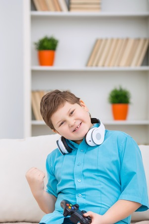 boyhood: Winning score. Chubby smiling boy in headphones is smiling and cheering while holding a joystick.