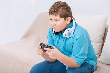 gamers: Game time. Chubby boy looks absorbed in video game while sitting on the sofa and playing. Stock Photo