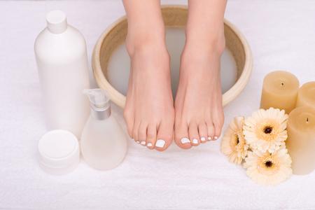 喜びの端。ビューティー サロンで足の治療を取得しながら水をボウルの端に立っている足のクローズ アップ