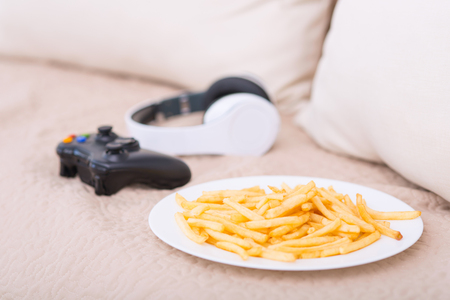plateful: Junk food. Plateful of fries along with joystick and headphones are resting on the sofa.
