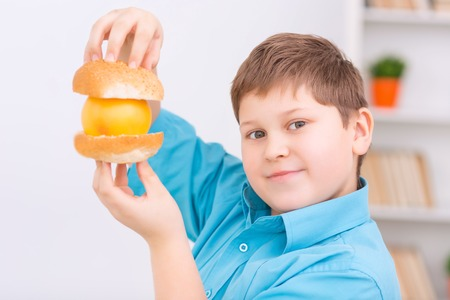 upholding: Healthy burger. Chubby boy is upholding a burger made of buns and orange