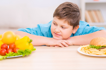 Healthy is better. Chubby boy is grinning while looking at plateful of tasty veggies.