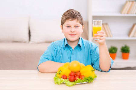 upholding: Healthy diet. Chubby boy is upholding a glass of juice while standing in front of veggies on the plate.