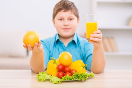 upholding: Organic fooding. Chubby boy is upholding an orange and glass of juice.