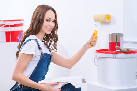 appealing: Decorating walls. Young appealing girl in male role is painting a wall.