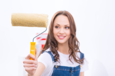 upholding: Absorbed in work. Young pleasant girl is upholding roller to paint a wall.