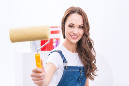 decorator: Decorator at work. Young attractive girl in male role is using a roller to paint walls.