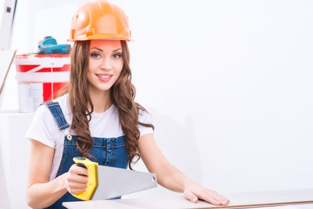 womanhood: Sawing procedure. Young attractive girl in male role is sawing a chipboard. Stock Photo