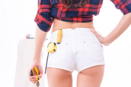Awesome view. Appealing female figure with various tools for renovation and measurement. Stock Photo