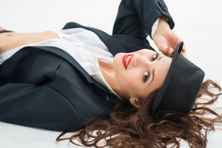 Girl in hat. Young attractive girl in male role is lying on white surface and wearing black hat.