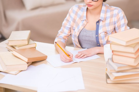 womanhood: Completing tasks. Female student is sitting at her desk and writing diligently. Stock Photo