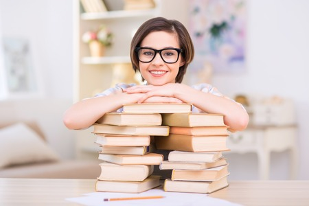 jovenes estudiantes: Girl with books. Young female student girl is leaning on a pile of her books and smiling.