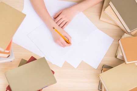 womanhood: Process of writing. Close up of human hands busy writing in the textbook. Stock Photo