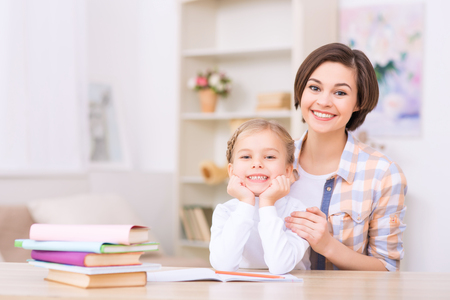 radiantly: Genuine smiles. Young mom and her charming daughter are smiling radiantly while sitting at the desk.